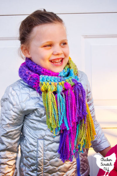 4 year old girl in silver coat wearing a rainbow colored hand crocheted scarf made with charisma yarn