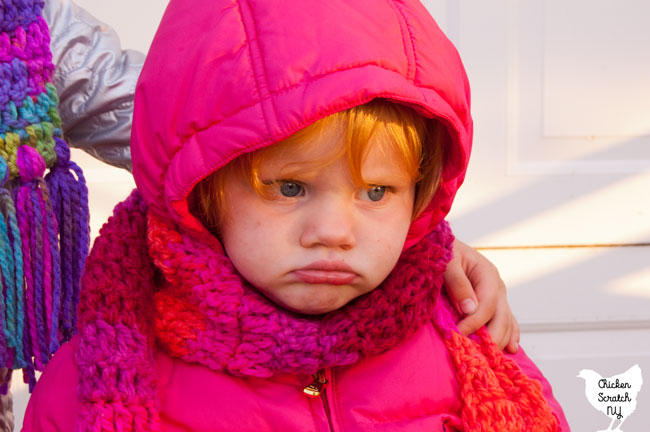 grumpy little blonde girl in puffy pink winter coat with hand crocheted pink and orange scarf