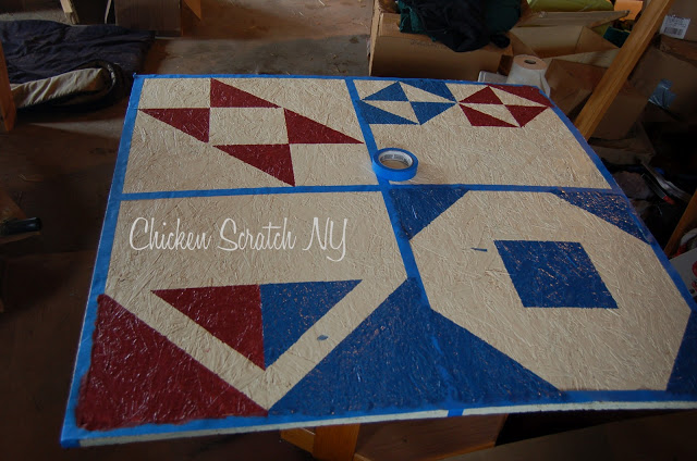 plywood sheet taped in a pattern and being painted to make a barn quilt