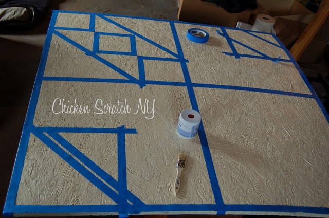 plywood sheet painted cream and maked with blue tape to make a barn quilt