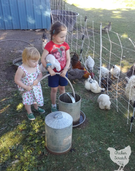 two little girls filling chicken wateres with a hose surrounded by chickens