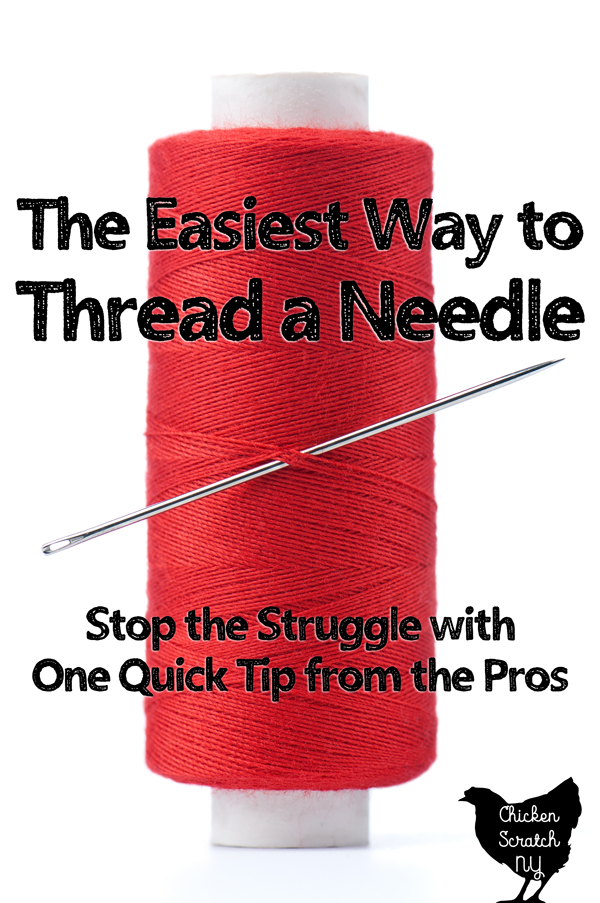 spool of red thread with a large silver needle stuck in the center with text overlay The easiest way to thread a needle