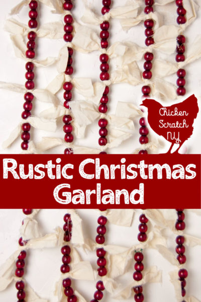 five strands of burgundy beads and unbleached muslin fabric over a white background