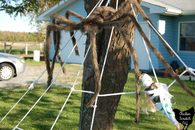 close up of halloween diy spider web decoration with large brown spider and barbie tied up with white fabric
