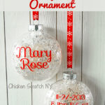 clear ornament filled with fake snow with red vinyl lettering for a childs name, birth date, birth weight, birth time and birth length