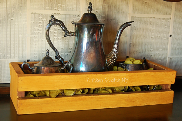 mustard yellow crate with wax finish holding metal teapot and sugar bowls in front of newspaper print walls