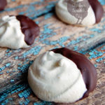 white vanilla meringue cookies dipped in dark chocolate on a blue and brown wooden backdrop