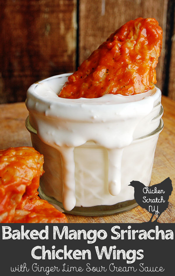 chicken wing with mango sriracha sauce in small small mason jar filled with white sour cream sauce