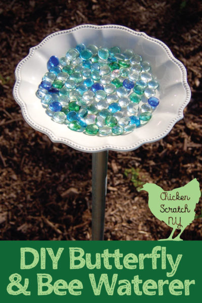 glass dish filled with blue and green glass gems on a metal pole for a DIY bee waterer