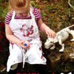 little blonde girl sitting on a stump wearing a white apron covered with red bloody hand prints holding an eyeball and petting a skeleton dog
