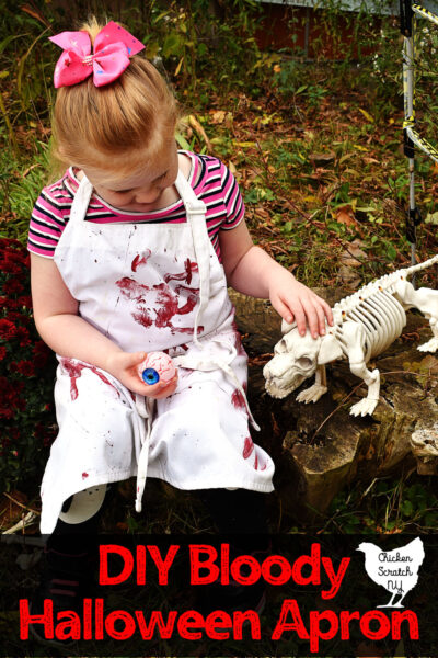 little blonde girl sittin on a stump wearing a white apron covered with red bloody hand prints holding an eyeball and petting a skeleton dog