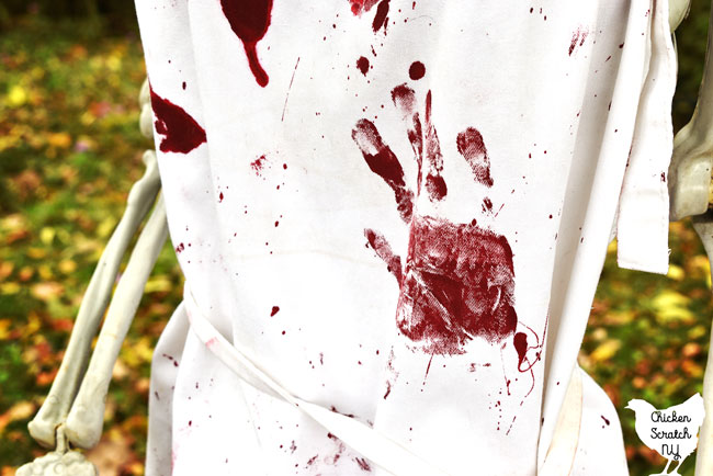 close up shot of white apron covered with bloody Halloween hand prints and blood splatters