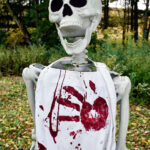life sized Halloween skeleton wearing a white Bloody Halloween Apron