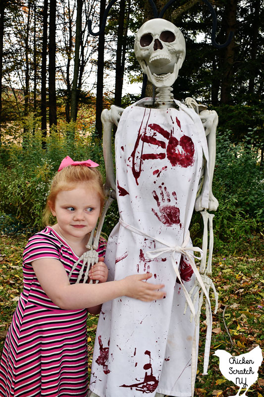 little blonde gold holding hands with a skelton wearing a bloody Halloween apron