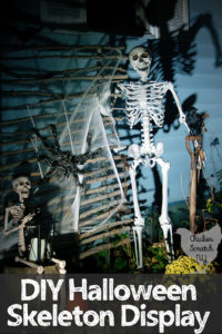 halloween skeleton display with life sized skeltion standing with shovel and crow, small skeleton sitting with lantern and skeleton hand sticking our of leaf pile by yellow mum