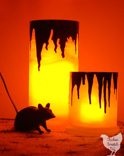 two candles holders light up with dark red drips that loop like blood on a spider sprinted burlap table cloth with a plastic rat