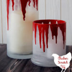 Frosted glass candle holders with fake blood dripping down and text overlay for DIY candle tutorial