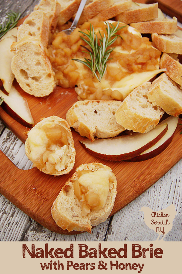 wooden cutting board sitting on white weathered wood surface with a baked brie covered in pear composte made with pears, honey and rosemany with slices of toasted crusted bread and sliced red pears