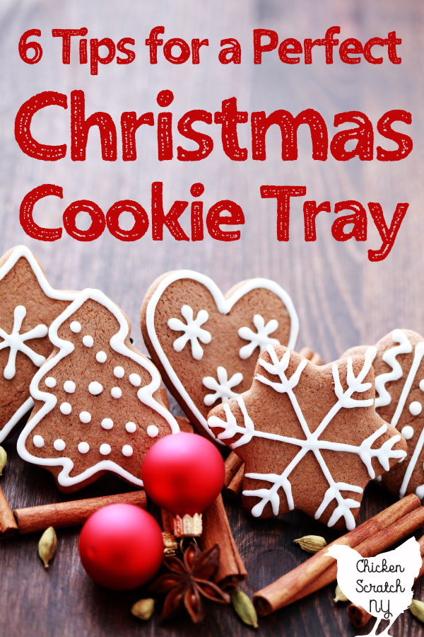 hazy wooden surface holding red Christmas bulbs and fancy gingerbread cookies decorated with white royal icing red text overlay 6 tips for a perfect Christmas cookie tray