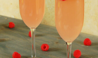 two raspberry peach mimosas in champagne flutes with lemon slices and red raspberries