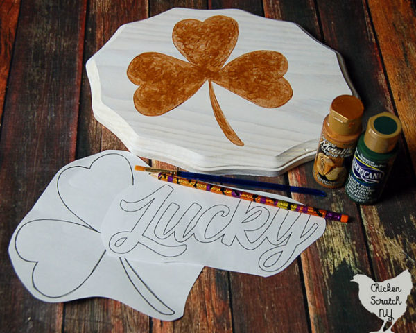 white wooden sign handpainted with a metallic gold shamrock and two paper stencils and green and gold paint