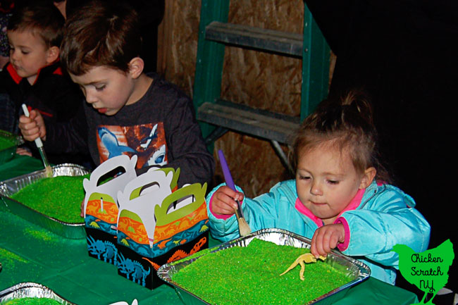 young boy and little girl using paintbrush to dig through green play sand for dinosaur bones