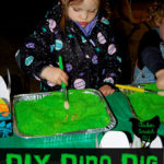little girl using paintbrush to dig through green play sand for dinosaur bones