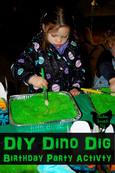 little girl using paintbrush to dig through green play sand for dinosaur bones
