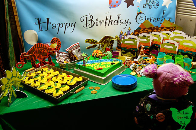 dinosaur birthday party dessert table with cupcakes, cake and party favors