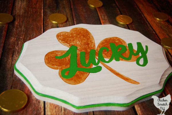 white wooden sign hand-painted with a metallic gold shamrock and the work lucky in green script