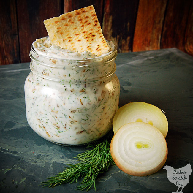 caramelized onion sip in a glass jar with fresh dill, pita chips and sliced onion on green tile