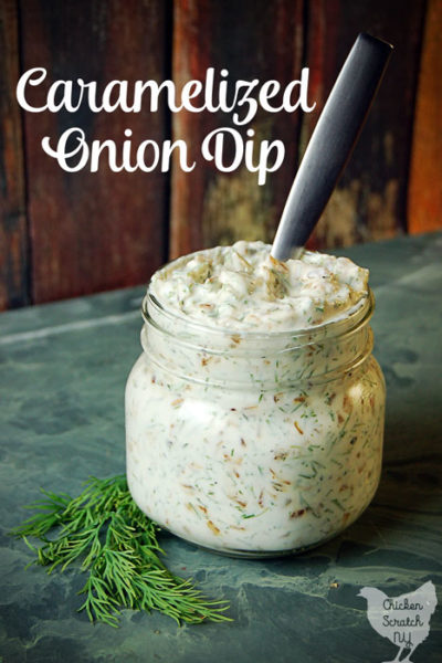 caramelized onion dip in a glass jar with fresh dill on green tile