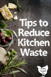 wooden board with olives, chees and herbs with text overlay Tips to Reduce kitchen waste