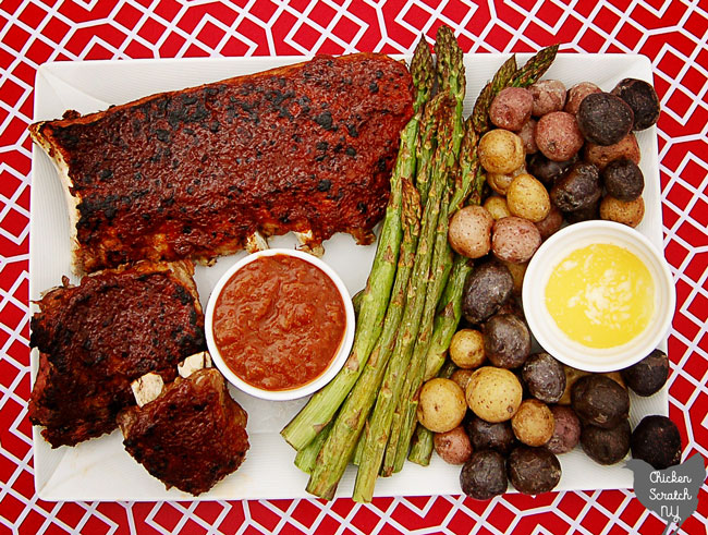 rhubarb BBQ sauce covered ribs on a white late on a red and white table cloth with a white dish filled with more BBQ sauce, broiled asparagus and red white and blue salt potatoes with a white dish of melted butter
