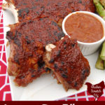 rhubarb BBQ sauce covered ribs on a white late on a red and white table cloth with a white dish filled with more BBQ sauce