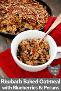 baked oatmeal with rhubarb, pecans and blueberries in a cast iron skillet with a scoop in a white cup with a copper spoon, on a red towel and rhubarb stalks on a grey stained wooden board