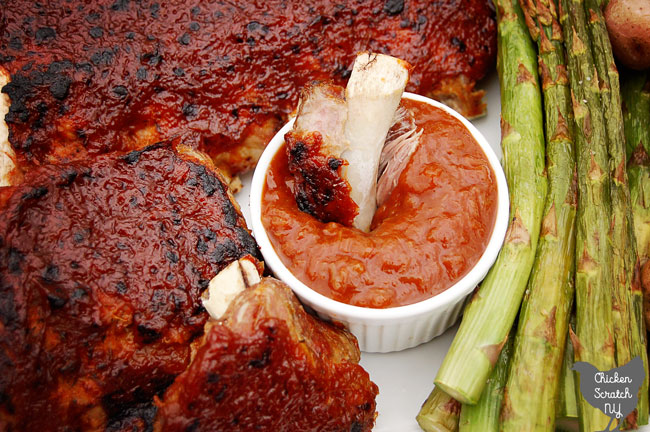 rhubarb BBQ sauce covered ribs on a white plate with a white dish filled with more BBQ sauce next to broiled asparagus