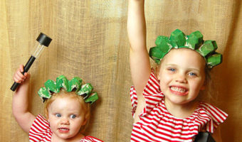 two little girls in red, white and blue outfits each wearing a handmade green statue of liberty crown holding a book and a solar lantern