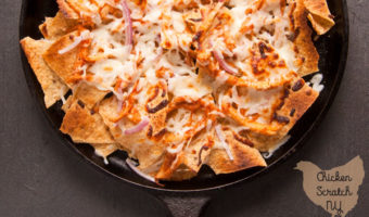 BBQ chicken nachos with red onion and mozzarella cheese on a cast iron griddle