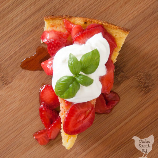 buttermilk cornbread topped with fresh strawberries and whipped cream with bail leaf on wooden cutting board