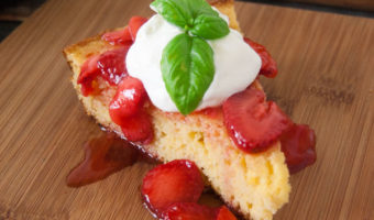 buttermilk cornbread topped with fresh strawberries and whipped cream with bail leaf on wooden cutting board with cast iron pan of cornbread and metal bowl of whipped cream in the back