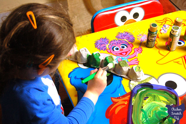 two girls painting egg cartons green at a sesame street table