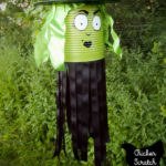 witch windsock made from a green painted tin can, black ribbon, green ribbons, a plate and funnel