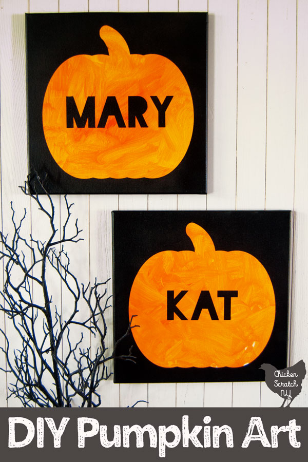white wall with two hanging black canvases with orange pumpkins and names in black block letters, one says MARY and the other says KAT with creep black branches in the corner