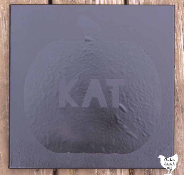 single canvas spray painted black with Pumpkin stencil with the name KAT in the center