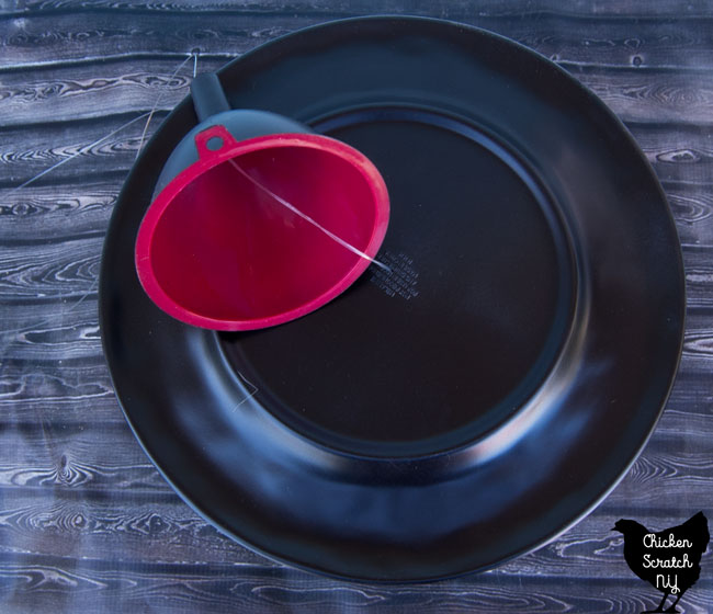 plastic plate painted black with a hole drilled in the center with a red funnel spray painted black stung together with fishing line