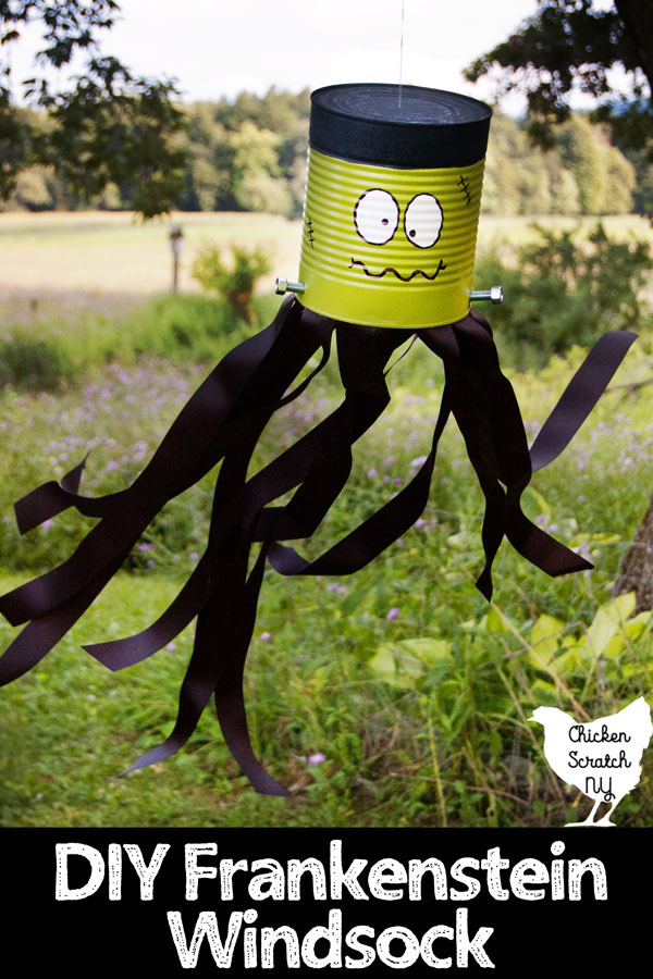 tin can turned into DIY Frankenstein Windsock with paint, screws and ribbon hanging in a tree with the black ribbon streamers blowing in the breeze