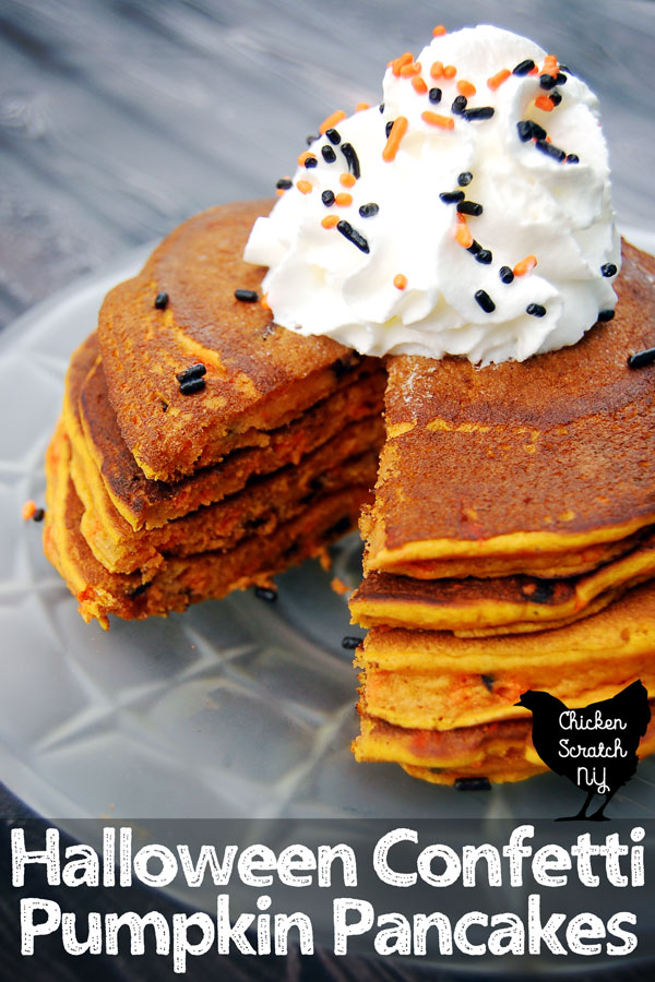 stack of Halloween confetti pumpkin pancakes filled with freamy pumpkins and black and orange sprinkles on a spiderweb frosted glass plate topped with whipped cream and more sprinkles