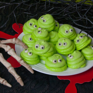 white plate full of lime green meringue cookies with eyes that look like Blobby from Hotel Transylvania on a black surface with red blood splatter coasters and a skeleton hand