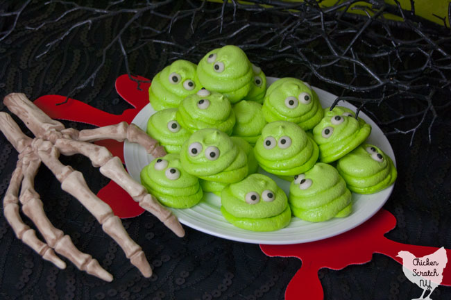 White Plate Full Of Lime Green Meringue Cookies With Eyes That Look Like Blobby From Hotel